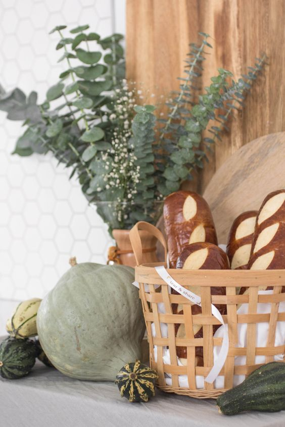 green pumpkins and gourds, eucalyptus in a vase and a basket with faux bread for cool rustic Thanksgiving decor