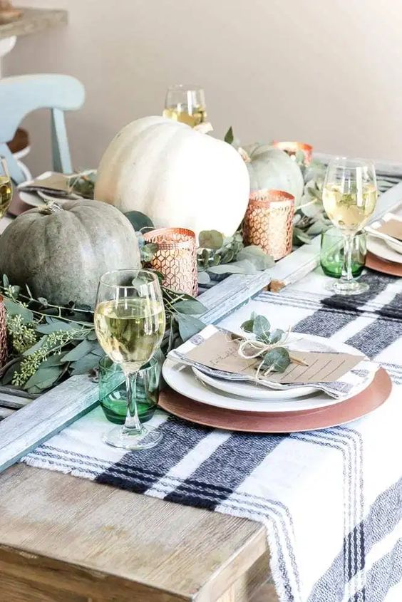 greenery, green and white pumpkins, candleholders, green glasses and greenery on the place settings for Thanksgiving