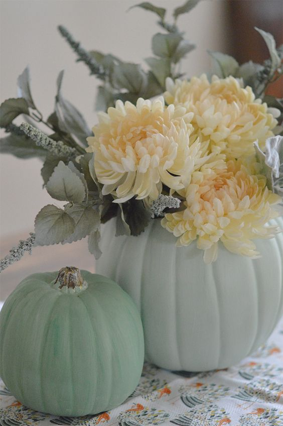 light green pumpkins, pale greenery and white blooms make up cool rustic decor for Thanksgiving