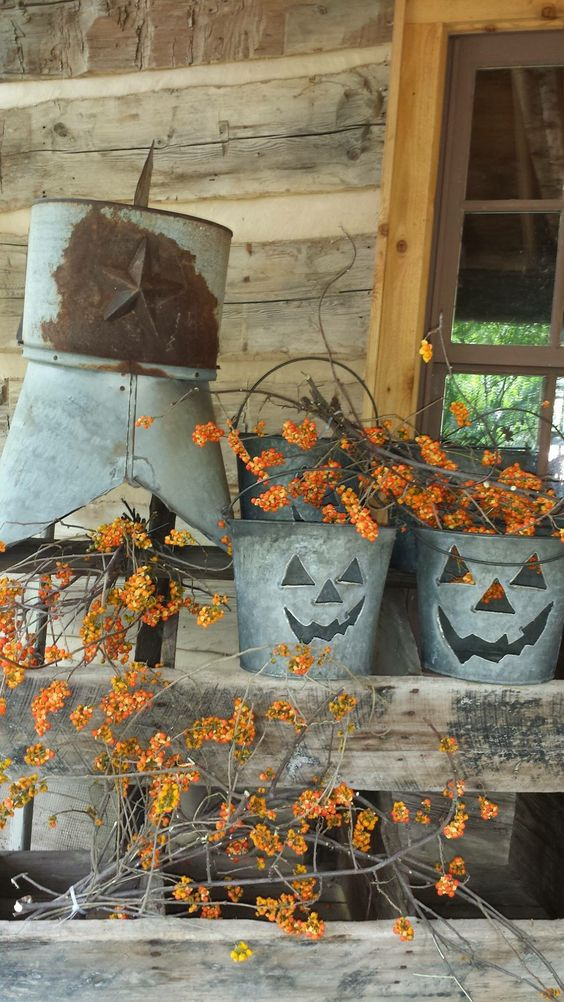 metal buckets with scary faces and lots of branches with berries for easy rustic Halloween decor