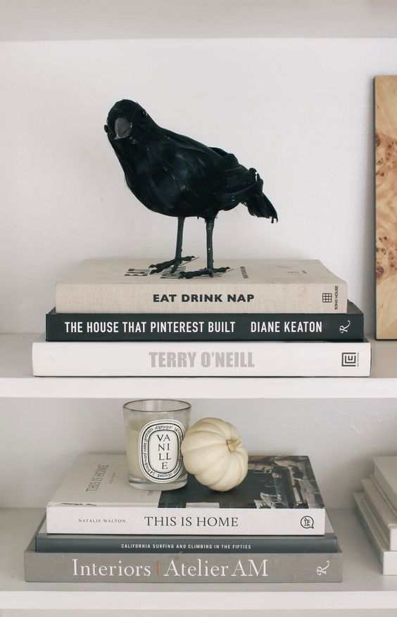 minimalist Halloween decor with a blackbird, a white pumpkin and a candle plus black and white books is awesome
