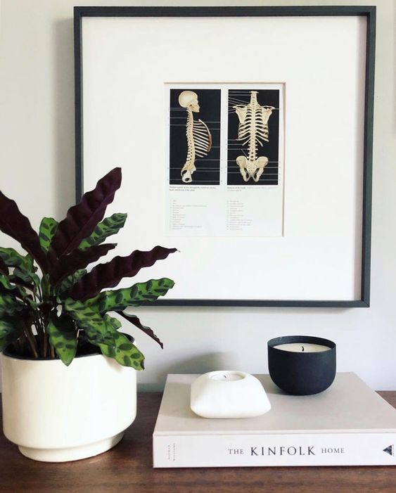 minimalist Halloween decor with a skeleton artwork and a candle in a black jar is a lovely and simple idea