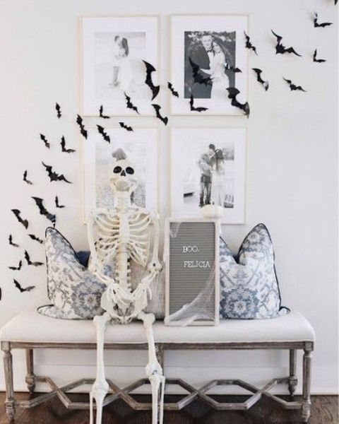 minimalist Halloween decor with black paper bats on the wall and gallery wall, a skeleton, a mini sign is lovely for minimal spaces