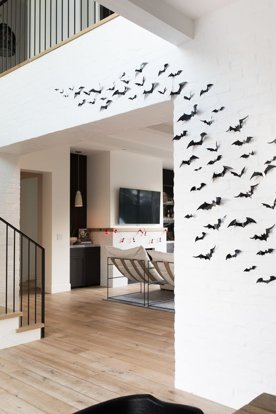 minimalist Halloween decor with black paper bats on the wall is eays to make last minute and looks cool and lovely