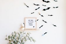 minimalist Halloween decor with black paper bats on the wall, mini pumpkins, lights and a greenery arrangement in a vase plus a sign