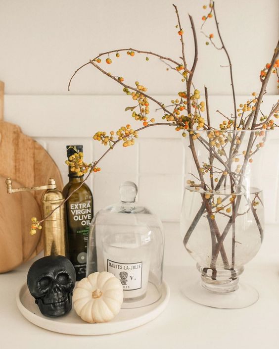 minimalist Halloween decor with branches with berries, a black skull, a white pumpkin is easy to realize and looks cool