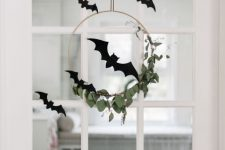 minimalist Halloween door decor with a wreath with greenery, black paper bats is a lovely idea for fall celebrating