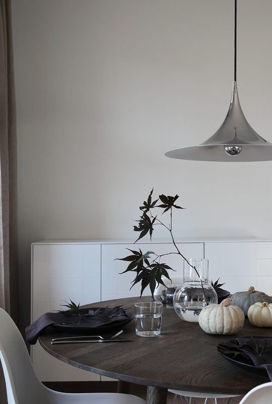 minimalist Halloween styling with natural heirloom pumpkins, greenery, black plates and black napkins is amazing