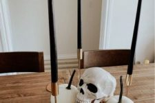 neutral pumpkins and black thin and tall candles in gold candlesticks are cool for minimalist Halloween decor