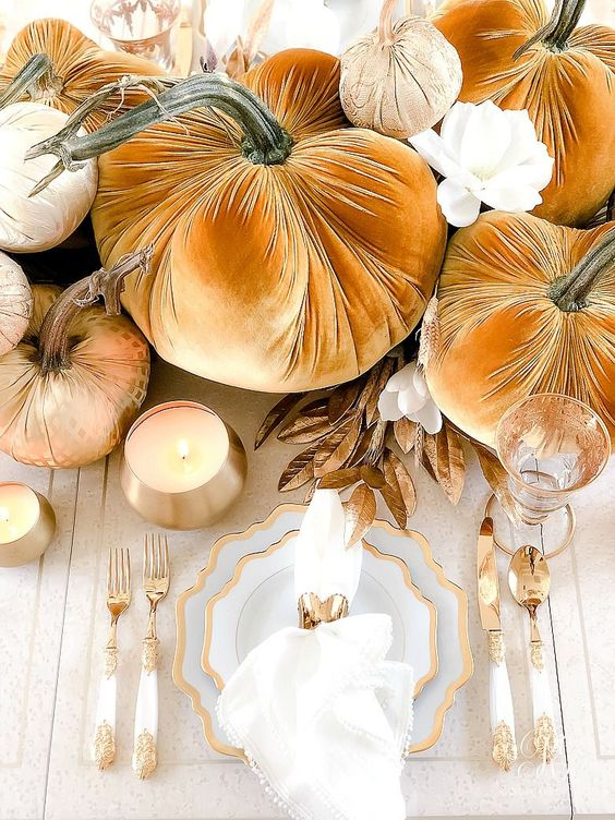 oddly shaped gold rimmer plates, gold and white cutlery, gold candleholders and glasses plus rust pumpkins for a wow Thanksgiving table