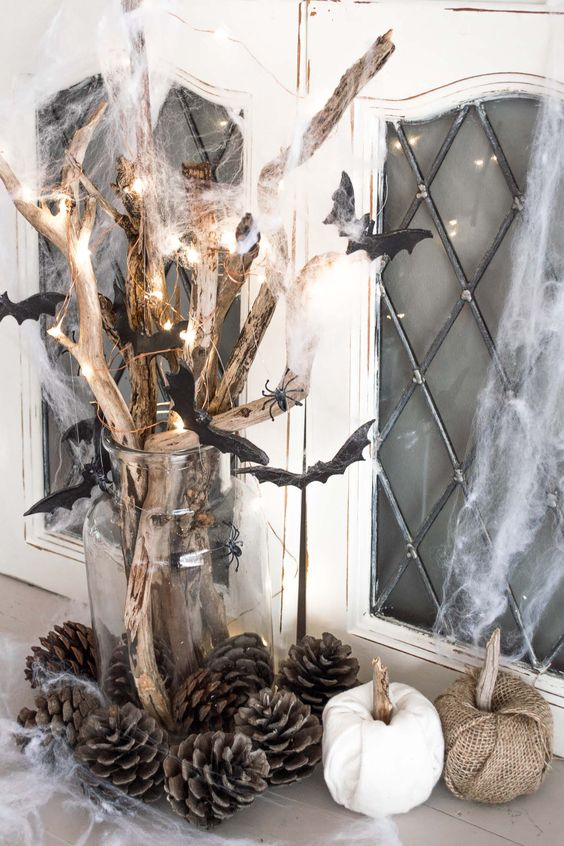 rustic Halloween decor of branches with lights, spiderweb and bats, pinecones and fabric pumpkins near the vase