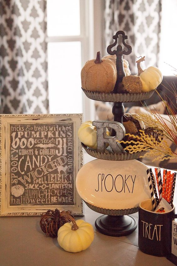 rustic Halloween decor with a metal tiered stand with pumpkins, a plate and a metal letter, pumpkins and a sign