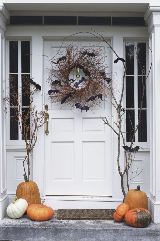 rustic Halloween porch styling with branches, pumpkins, a vine wreath with bats is a simple and cool idea