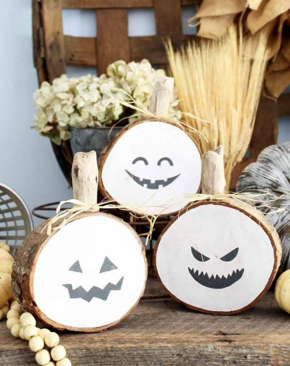 rustic Halloween pumpkins of wood slices with spooky faces, hay and wooden beads for Halloween decor