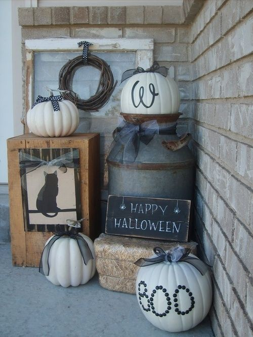 rustic Halloween styling with hay, white pumpkins with black bows, a wooden box with a cat and a vine wreath