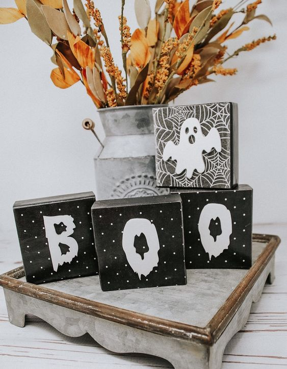 rustic Halloween styling with wooden cube letters, a ghost, a bright dried arrangement in a metal churn