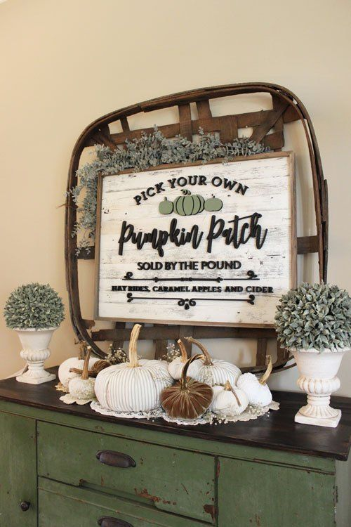rustic Thanksgiving decor with greenery, a basket with a sign, white and rust colored pumpkins feels vintage and chic