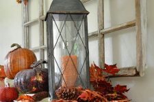 rustic vintage Thanksgiving decor of bright leaves, pinecones, pumpkins and dried leaves and berries over the table