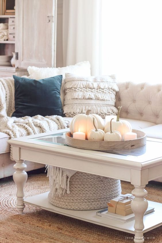 simple and cool Thanksgiving decor with a wooden tray, white candles and pumpkins, a basket with neutral blankets