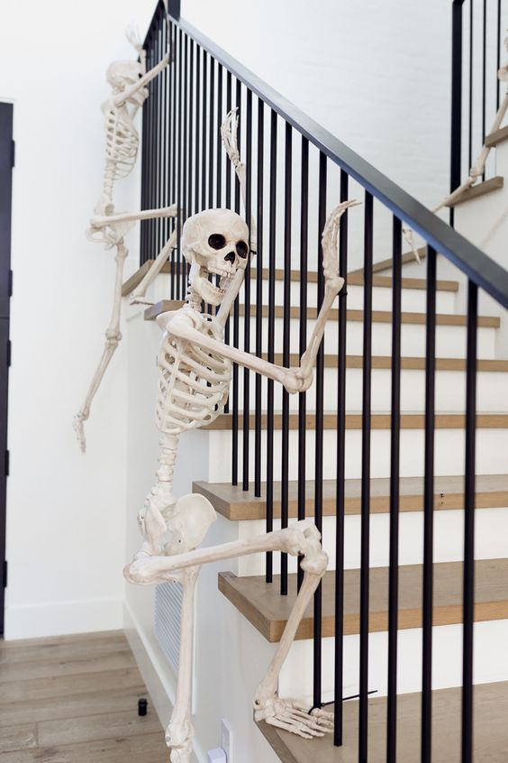 skeletons climbing up the railing are a fun and very easy idea to style your home for Halloween and you can realize that very quickly
