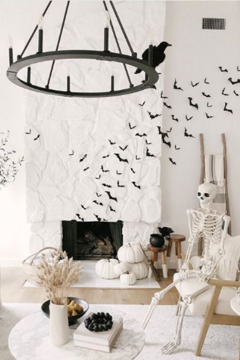 stacked white pumpkins, a skeleton on  a chair, black bats and blackbirds are amazing to style your space for Halloween