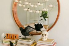 stylish minimalist Halloween decor with blackbirds, a skull and a garland of mini white pumpkins is very chic and cool