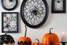 vintage Halloween console styling, with white doilies in black frames, spiders, bold pumpkins with polka dots and in doilies plus a candle