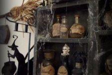 vintage Halloween decor – a black storage unit with vintage potion bottles, spider web, vintage books and skeletons is a chic idea