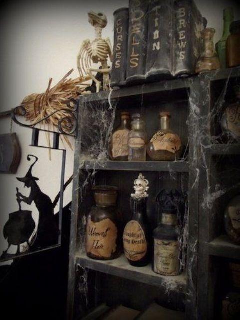 vintage Halloween decor   a black storage unit with vintage potion bottles, spider web, vintage books and skeletons is a chic idea