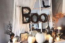 vintage Halloween decor in black and white, with a vintage mirror, some spiderweb, white pumpkins and candles, leaves and branches
