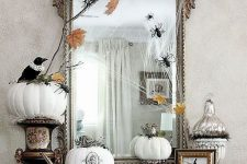vintage Halloween decor with a large mirror in an ornated frame, white pumpkins with patterns and blackbirds plus spiders and fall leaves