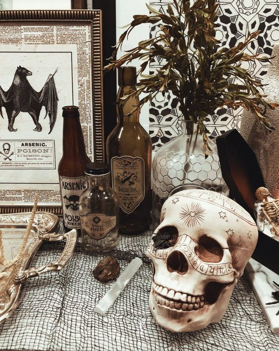 vintage Halloween decor with a patterned skull, poison bottles, greenery, vintage signs and artworks is easy to recreate yourself