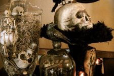 vintage Halloween decor with jars and cloches with skulls and skeletons, a skull on a stand, some candles and a blackbird