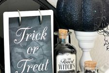 vintage Halloween decor with a sign, vintage potion bottles, white stands with black glitter pumpkins is a chic and bold idea