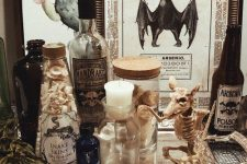 vintage apothecary Halloween decor with a rat skeleton, apothecary bottles, signs and a silver tray is cool and chic