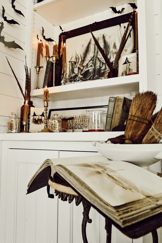 vintage rustic Halloween decor with feathers, brooms, a spellbook, candles and bats around is a beautiful idea to go for