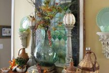 vintage rustic Thanksgiving decor with dried leaves, woven bottles, wooden stands with pumpkins, berries and leaves