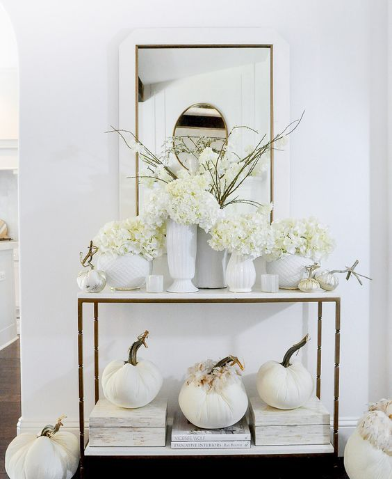 white Thanksgiving decor with fabric pumpkins and feathers, white vases and blooms is a beautiful idea for fall
