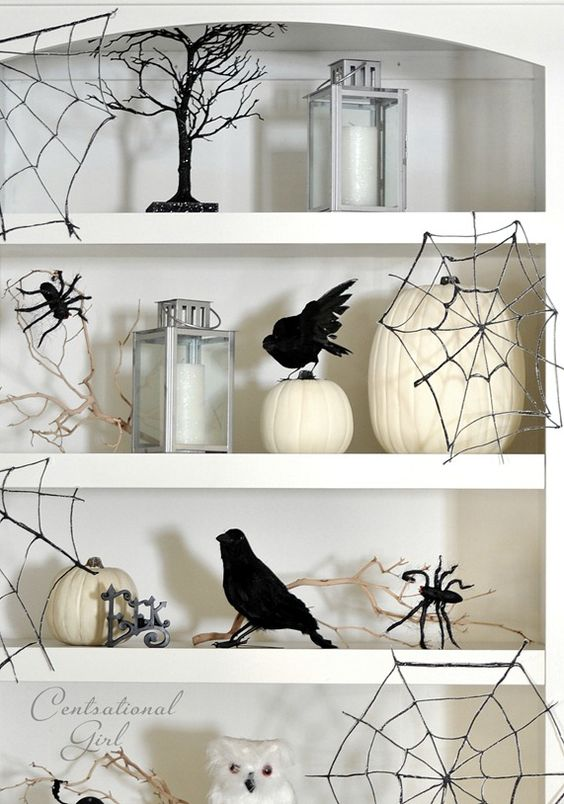 white niche shelves styled with white pumpkins, candles, owls, blackbirds, black spider web and black spiders are perfect