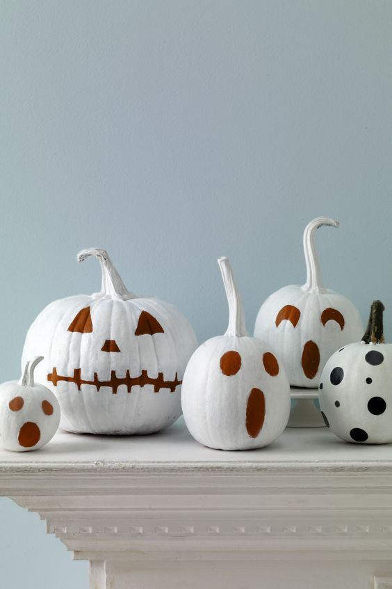 white pumpkins with faces painted isntead of carving is a great and fast DIY you can easily realize
