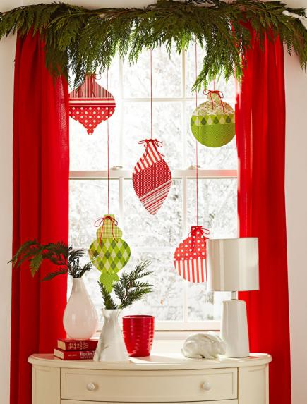 make some oversized christmas ornaments from craft paper to make your windows decor visible from outside