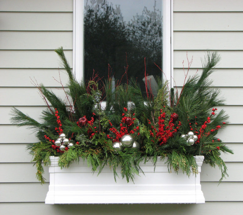 fill a flower box with holiday decorations like evergreen twigs berries and ornaments