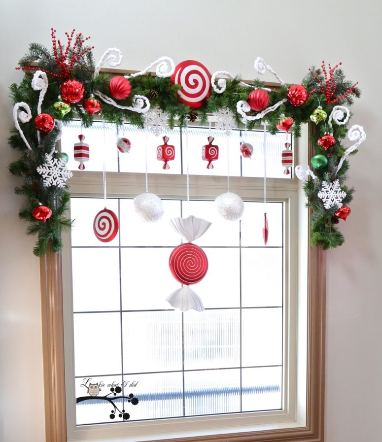 Faux candies in red-white tones would become a great addition to an evergreen swag topping the window.