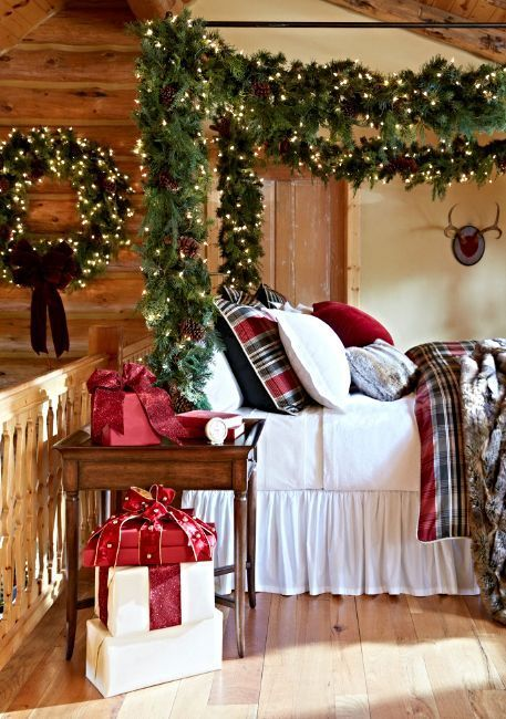a Christmas bedroom with evergreens, lights, pinecones and large gift boxes that will make you feel very holiday-like