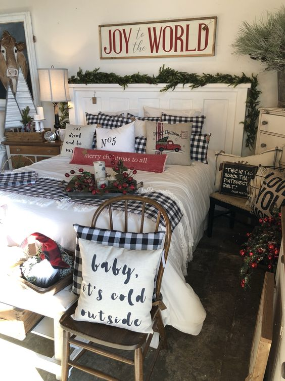 a Christmas bedroom with plaid bedding, evergreens and pinecones, berries and branches for a more natural feel