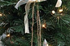 a Christmas ornament of silver glitter bells, white ribbon bows is an easy decoration that you can DIY
