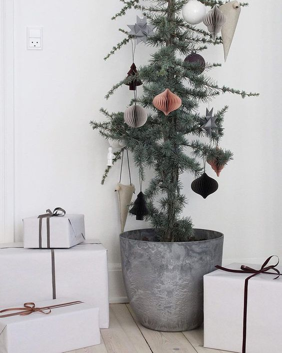 a Christmas tree in a metal pot with 3D paper ornaments is a stylish and chic idea
