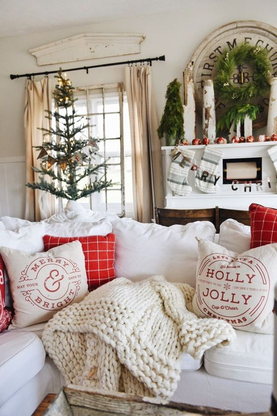 a Christmas tree with a banner, a greenery wreath, a mini tree, apples and a letter banner plus red and white pillows