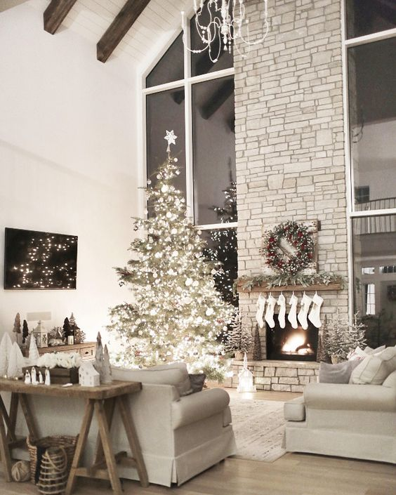 a Christmas tree with lights and white ornaments, white stockings, a fir garland and a fir wreath with red berries and mini trees