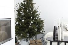 a Christmas tree with silver and clear ornaments and an arrangement of black and white candleholders for a Nordic feel
